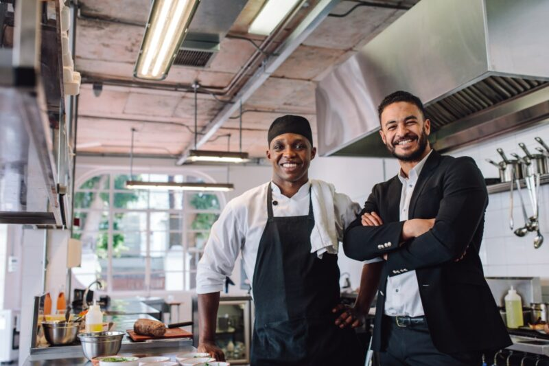 Two black men, one in suit and one in chef shirt and apron, smiling inside commercial kitchen