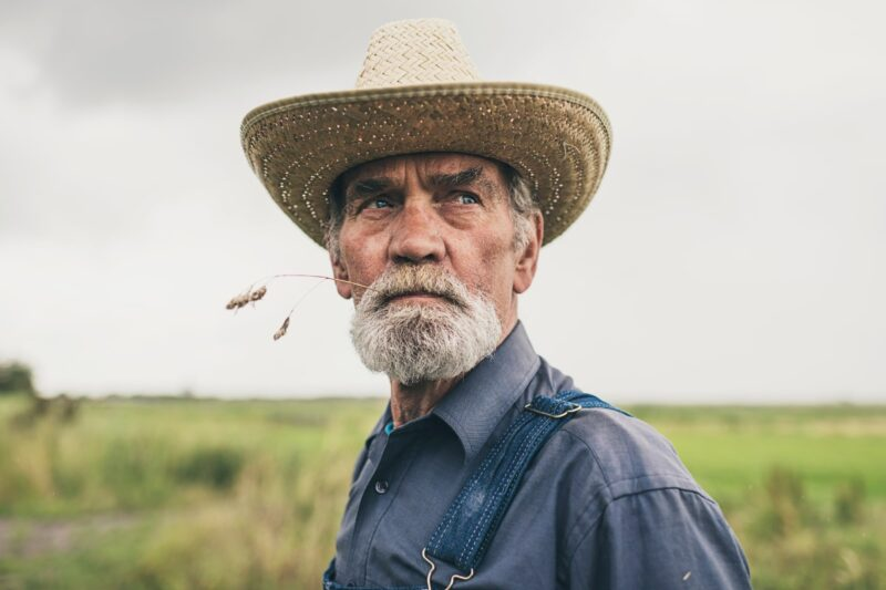 Older white man farmer with whicker hat and wheat stem in mouth