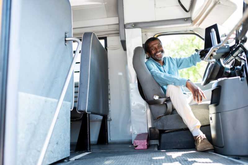 Black man bus driver sitting in seat and smiling at camera