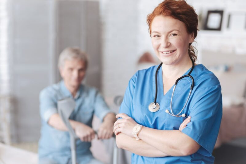 White female nurse in blue scrubs in foreground with white male patient blurred in background